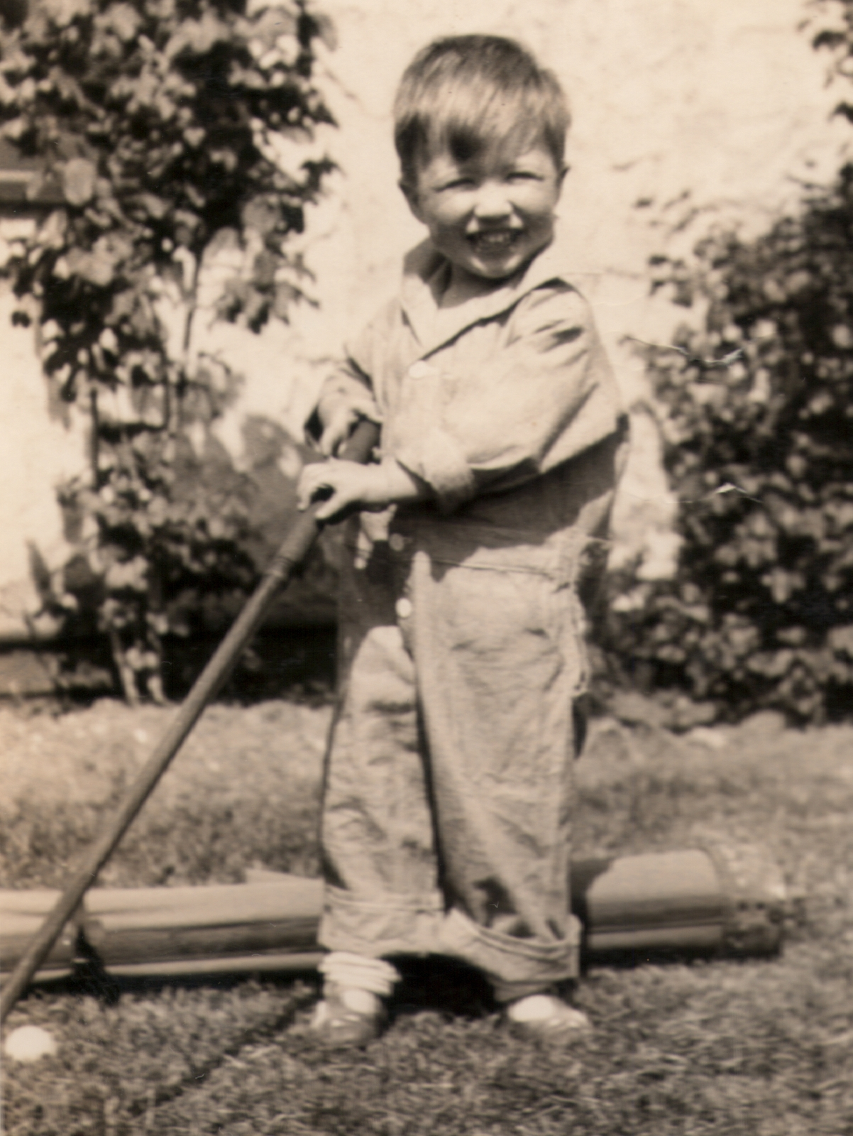 My father trying golf in 1927, with a corner of my grandmother's rose garden in the background.