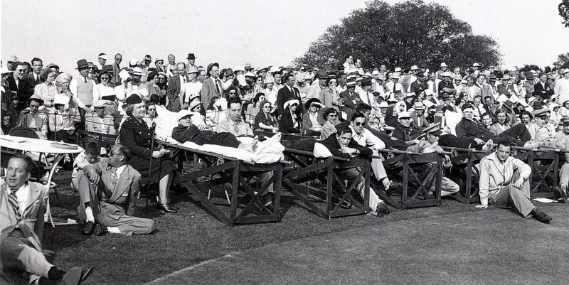 Wounded soldiers watching the Masters from litters placed beside the eighteenth green in 1947. The club gave them free tickets and preferred seating.